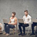 Junger Mann in Zeitleiste von arm zu reich, während er an einem Laptop arbeitet