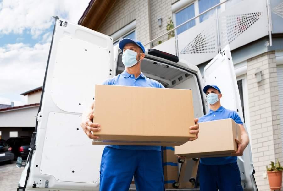 Zwei Mitarbeiter eines Umzugsunternehmens stehen mit Mund-Nasen-Schutz und Kisten hinter einem Transporter vor einem Haus