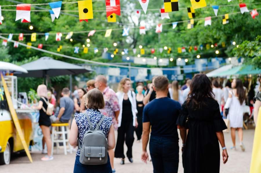 Menschen auf einem Street Food Festival, über ihnen sind kleine Fahnen gespannt