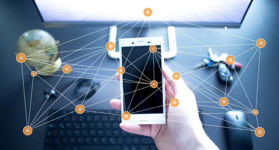 Im Bildvordergrund hält eine männliche Hand ein Smartphone, angedeutete Vernetzung mit Gegenständen auf einem Tisch aus der Vogelperspektive mit Computerbildschirm, Maus, Tastatur, Globus, Schlüsselbund und Kabel