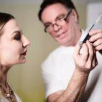 Dr. Karsten Lange erklärt einer Patientin ein Instrument für einen schönheitschirurgischen Eingriff