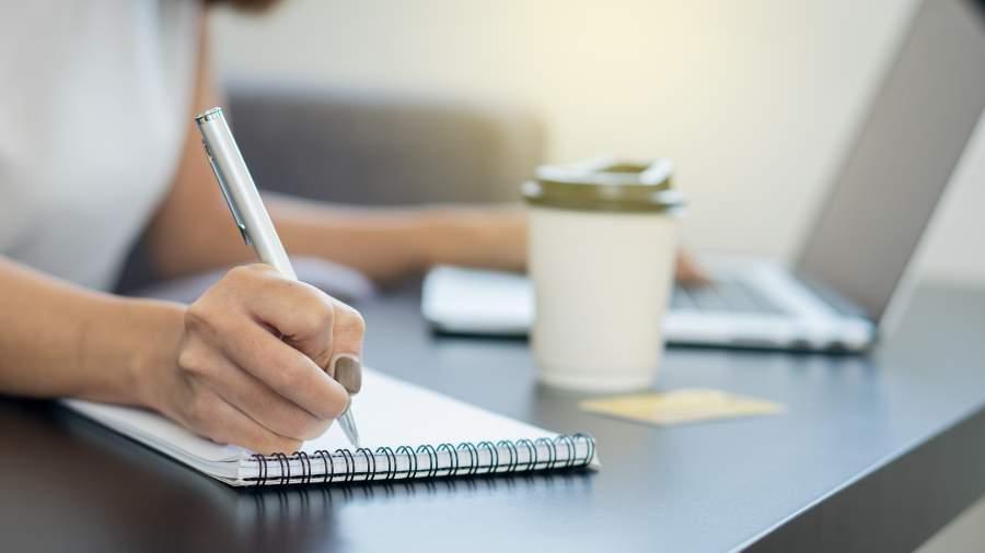 Person arbeitet am Laptop und macht handschriftliche Notizen mit Stift und Block, ein Kaffeebecher steht auf dem Tisch