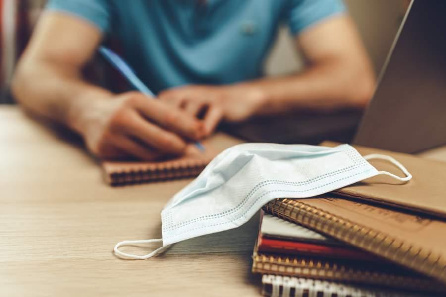 Mann sitzt vor Laptop und macht handschriftliche Notizen auf einem Block, im Vordergrund sind weitere Bläcke und ein Mundnasenschutz zu sehen