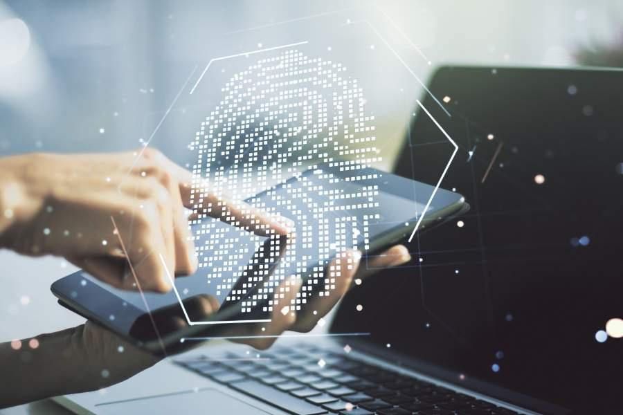 Digitaler Fingerabdruck, im Hintergrund bedienen zwei Hände ein Tablet vor einem Laptop