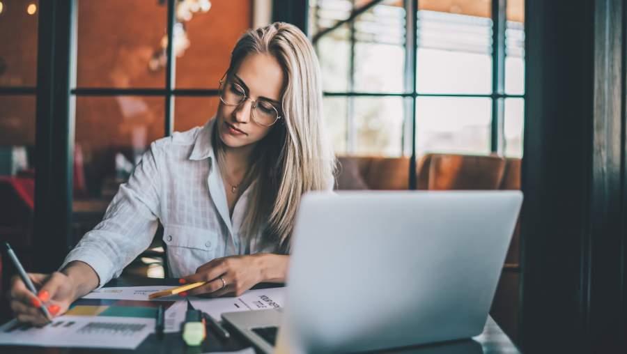 Junge Frau arbeitet konzentriert mit einigen Unterlagen und Laptop