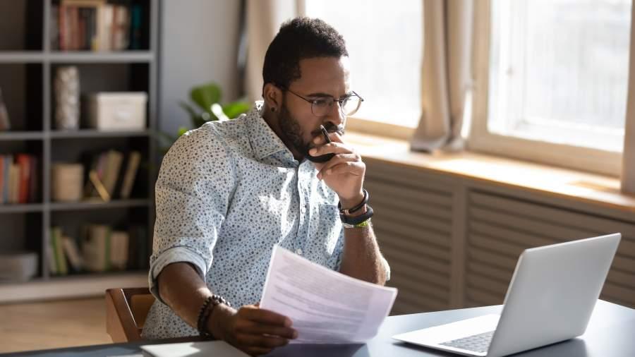 Junger afro-amerikanischer Mann sitzt an Laptop mit Unterlagen und überlegt