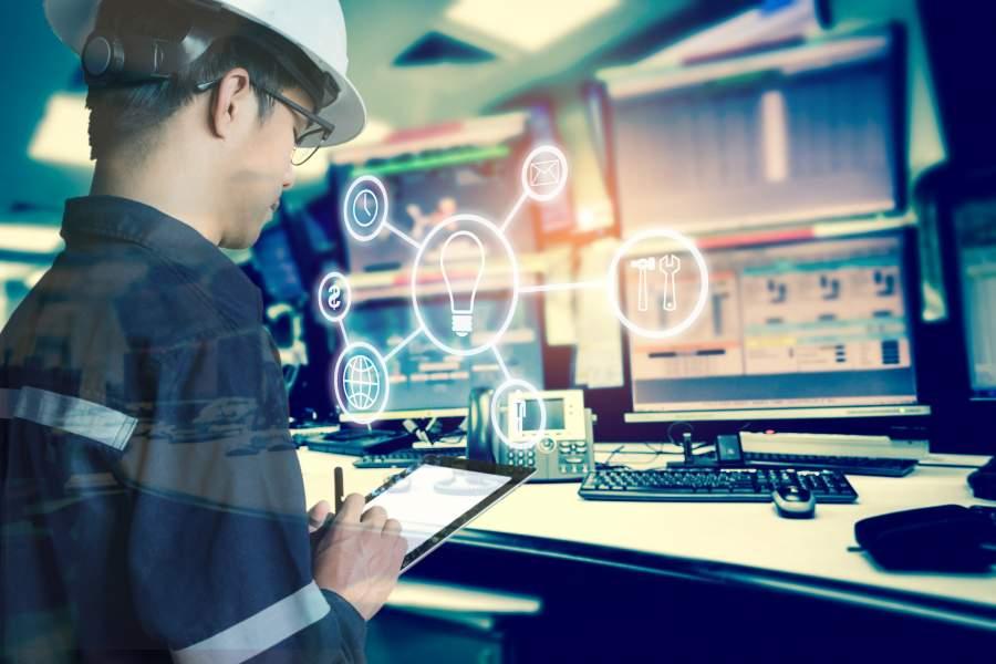 Facharbeiter in Schutzkleidung und Helm arbeitet mit digitalen Daten mit Tablet, mehrere Bildschirme an Büroarbeitsplatz im Hintergrund