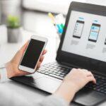 Person hält Smartphone in der Hand und arbetiet an Laptop mit App-Programmier-Bildschirm am Schreibtisch