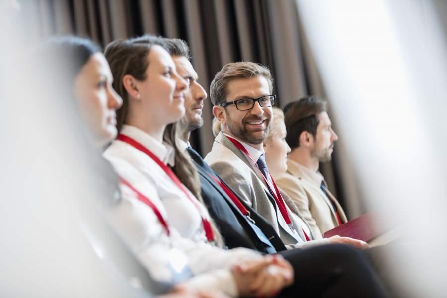 Gut gelaunte Menschen in Business-Kleidung in einem Vortragssaal und tragen Berechtigungskarten an Schlüsselbändern um den Hals, ein Mann mit Brille lächelt in die Kamera