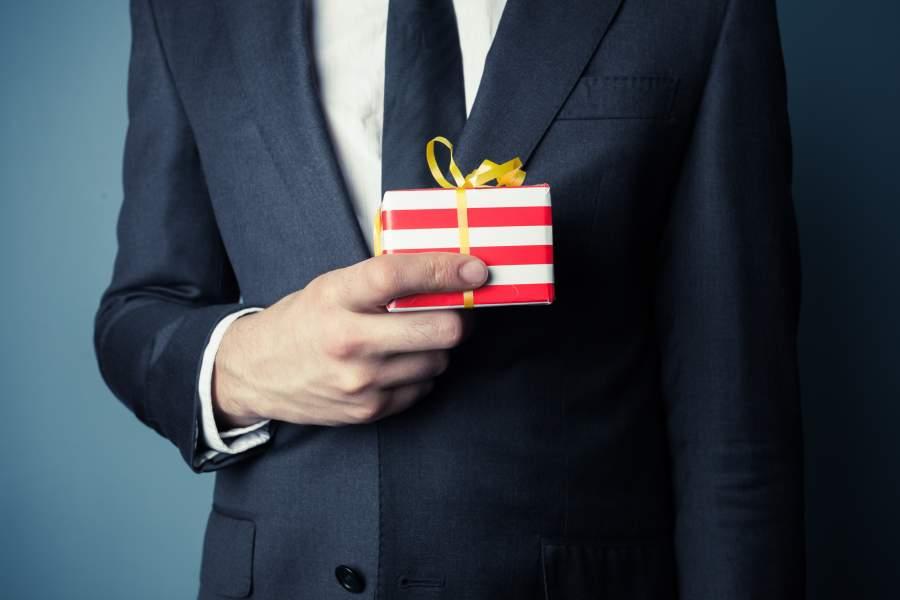 Geschäftsmann hält ein kleines eingepacktes Geschenk mit Schleife auf Brusthöhe