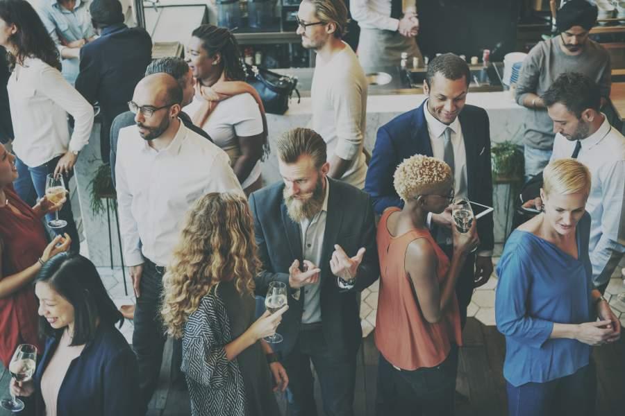 Diverse Personen in Business Casual Look in einem Foyer bei Business-Veranstaltung