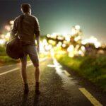 Junger Mann mit Reisetasche steht auf einer Asphaltstraße vor einer Stadt und betrachtet die Skyline