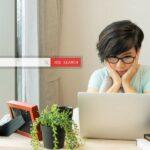 Junge Frau sitzt vor dem Laptop mit einem frustrierten und verzweifelten Gesichtsausdruck, auf dem Tisch stehen einige Zimmerpflanzen, darüber schwebt ein Eingabefeld mit der Beschriftung Job Search