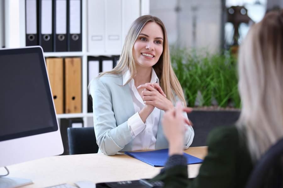 Junge Frau lächelt in einem Bewerbungsgespräch mit Personaler*innen am Schreibtisch gegenüber