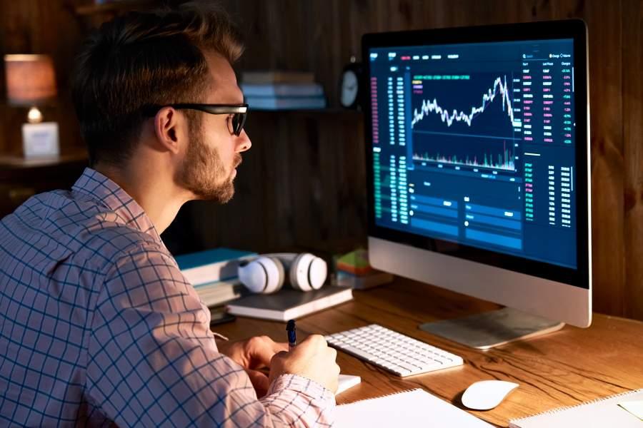 Mann in kariertem Hemd und Brille betrachtet den Kurs einer Crypto-Währung auf einem Monitor und macht sich handschriftliche Notizen