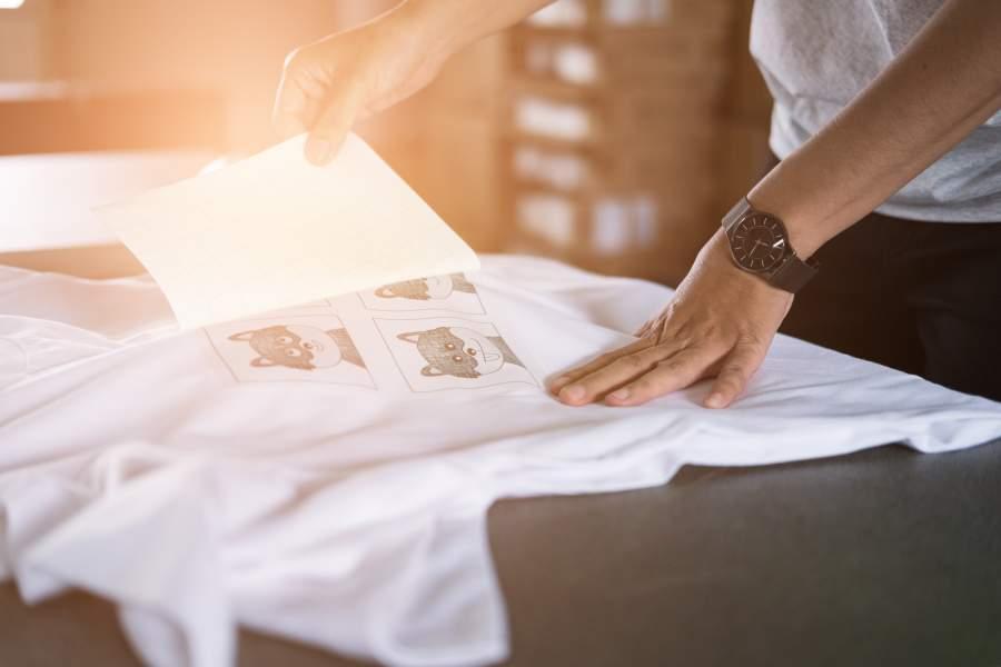Junge Frau bringt einen Cartoon-Textildruck auf ein T-Shirt auf
