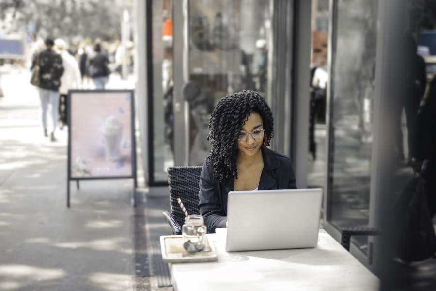 Junge Frau arbeitet an einem Laptop im Außenbereich eines Straßencafés