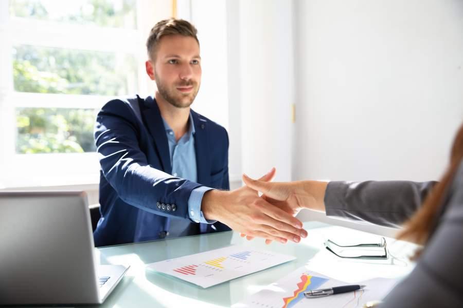 Junger Mann in hellem Meetingraum streckt die Hand zum Handshake mit seiner weiblichen Verhandlungspartnerin gegenüber vom Tisch aus