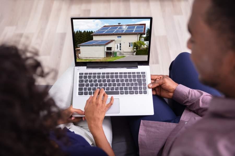 Junges diverses Paar sieht sich auf einem Laptop das Bild eines Immobilien-Neubaus mit Solaranlage an