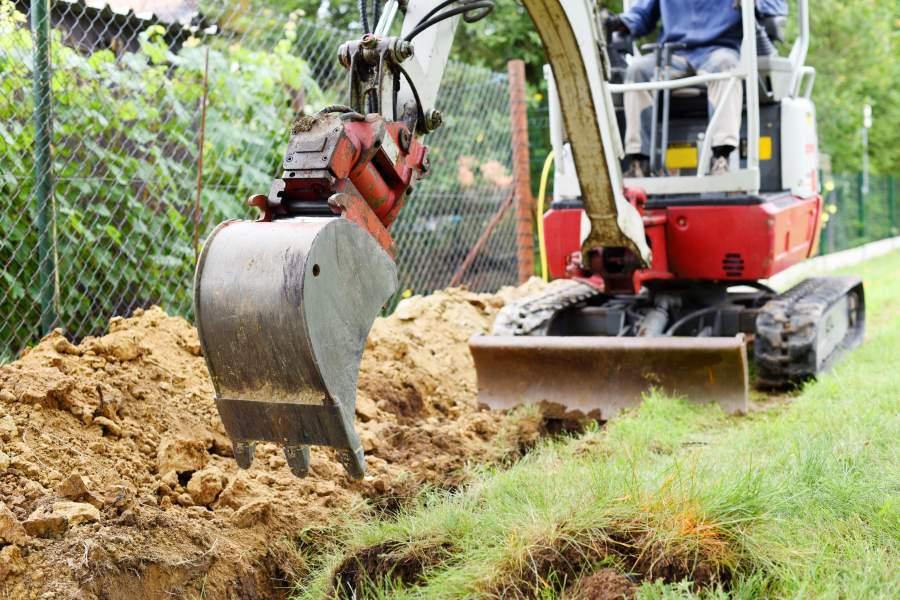 Mann bedient einen Minibagger in privatem Garten und hebt eine Grube neben dem Maschendrahtzaun aus