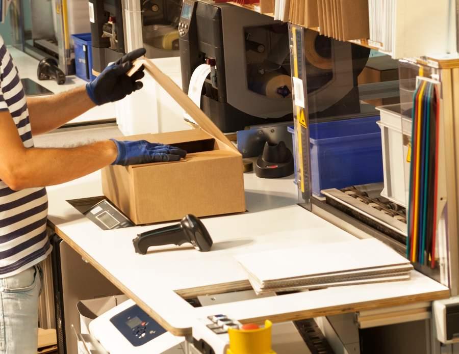 Mitarbeiter*in bei Warenkommissionierung an Packtisch für den Paket-Versand