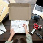 Frau bereitet Produkte aus Onlineshop für Versand vor, Vogelperspektive auf Tisch mit offenem Paket mit Karte, Paketklebeband, Schere, Cuttermesser, Versandtaschen, Stempel, Laptop, Notizblock und Stift