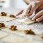Jemand formt und füllt frische Ravioli in sorgfältiger Handarbeit