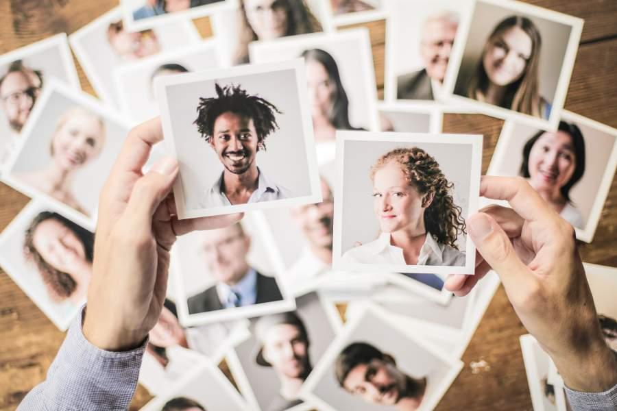 Vogelperspektive auf mehrere Fotoaufnahmen von verschiedenen / diversen Menschen, Hände halten zwei Bilder im Vordergrund wie zum Vergleich