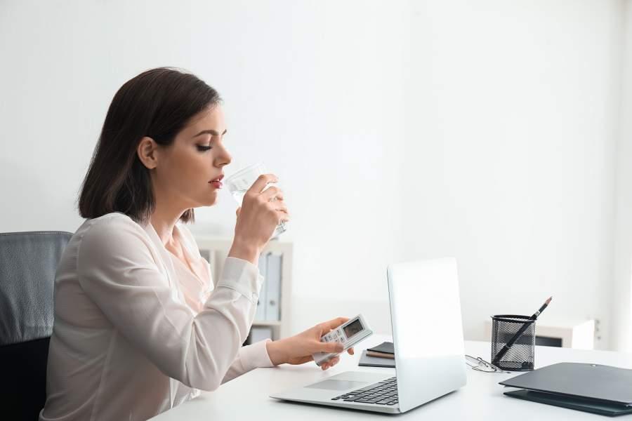 Junge Frau in Büro sitzt an Schreibtisch mit Laptop, Unterlagen und Stiften und trinkt ein Glas Wasser