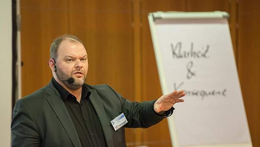 """Torsten Werner im Vortrag mit Mikrofon und Namensschild vor einer Flipchart, Schriftzug """"Klarheit und Konsequenz"""""""