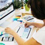 Frau arbeitet an professionellem Webdesign und sichtet Design-Skizzen