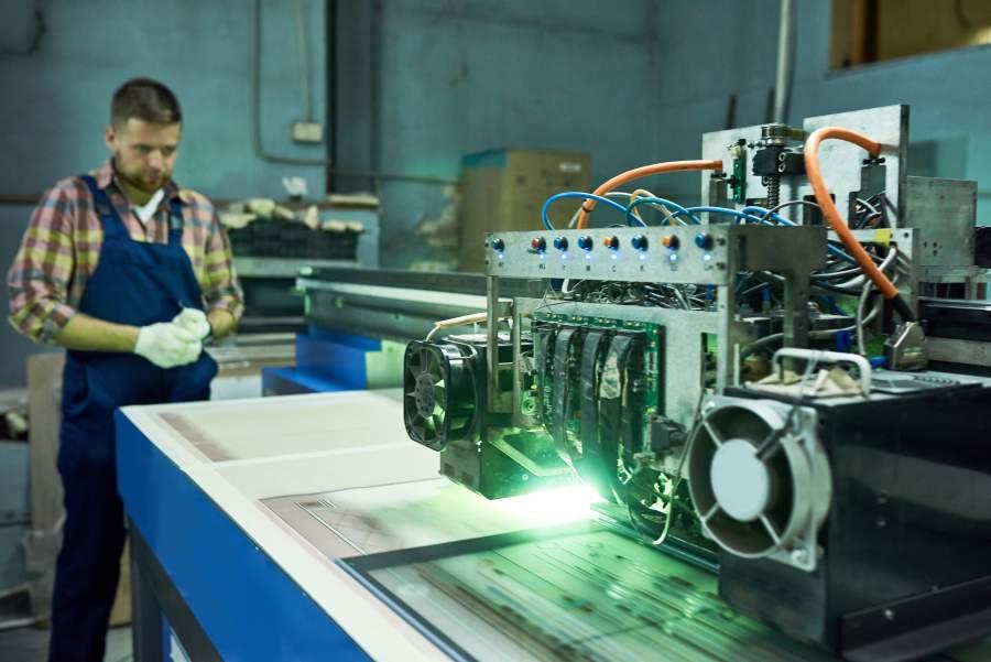 Arbeiter überwacht eine Lasermaschine bei Gravierarbeiten in einer Werkhalle