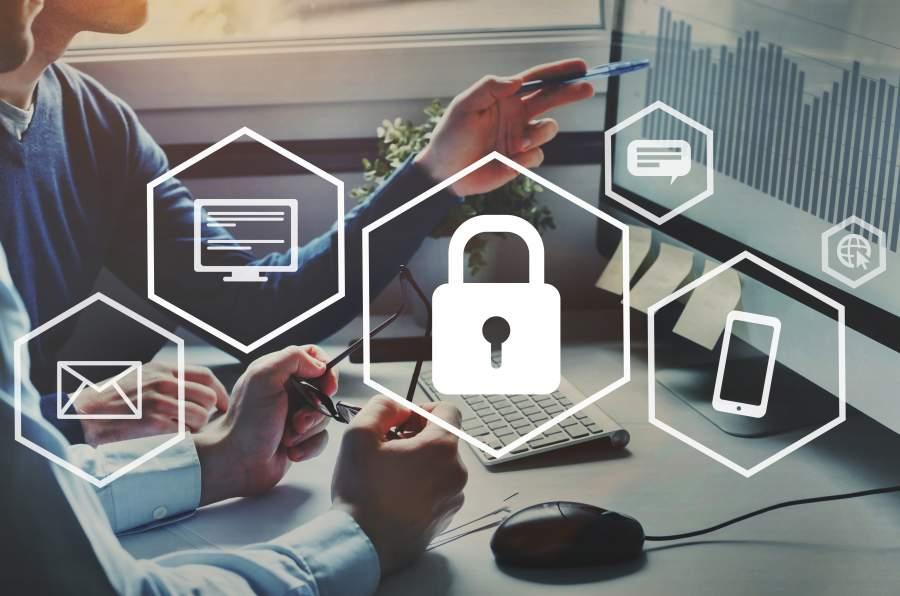 Zwei Geschäftsleute an einem Büroarbeitsplatz besprechen Diagramm-Informationen auf dem Bildschirm, im Vordergrund verschiedene Icons: Vorhängeschloss / Datensicherheit, Smartphone, Nachrichten, Digitale Daten, Messenger, Webzugriff
