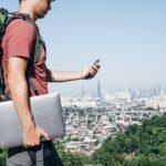 Digitaler Nomade mit rgoßem Rucksack und Laptop blickt aufs Handy, im Hintergrund eine Stadt-Skyline