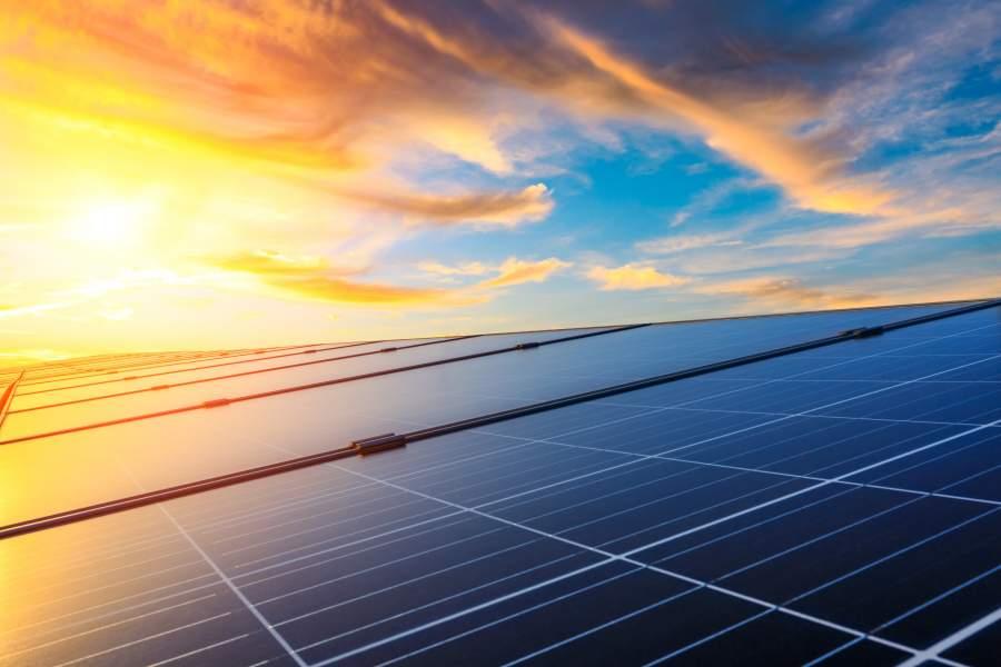 Landschaft mit Solaranlagen und Sonnenuntergang mit Wolkenhimmel