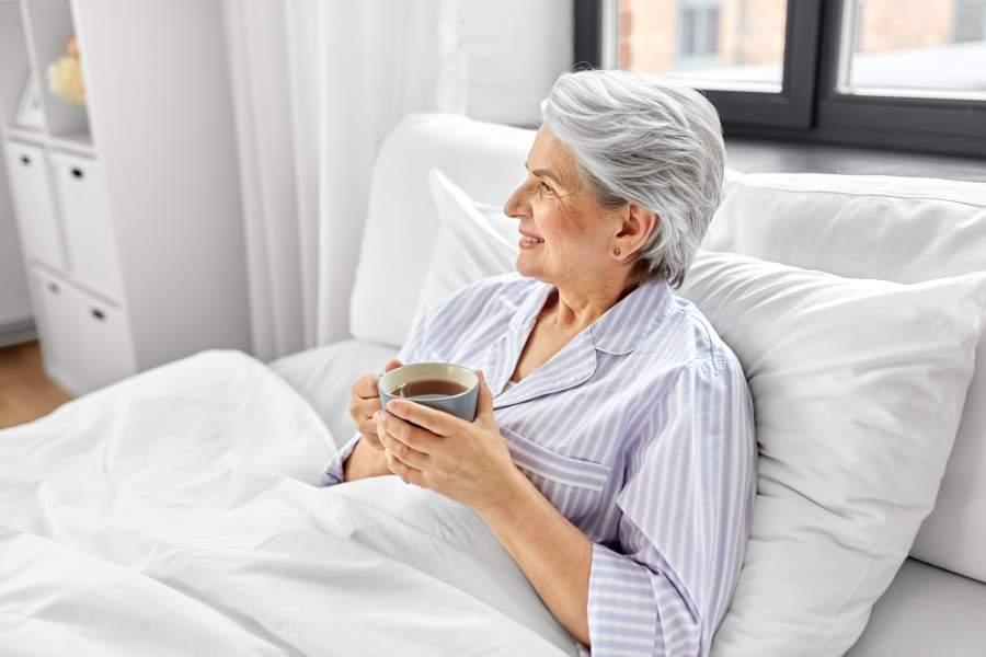 Ältere Frau sitzt im Bett mit weißer Bettwäsche und trinkt Kaffee
