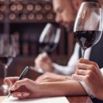 Eine Sommelière beim Weintasting und bei der schriftlichen Bewertung des Rotweins im Glas, im Hintergrund ein Sommelier