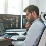 Mann in Business-Hemd in einem hellen Büro mit mehreren Bildschirmen betrachtet Aktienkurse