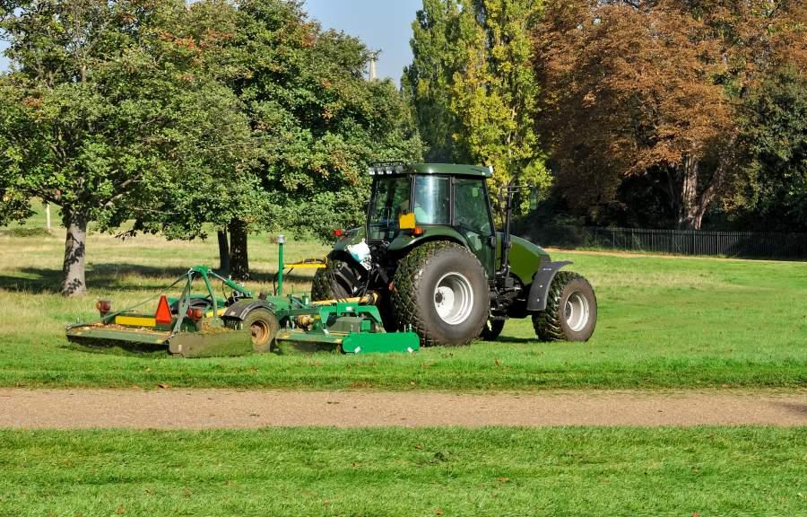 Traktor bei Pflegearbeiten auf Grünanlage, Mähen von Gras