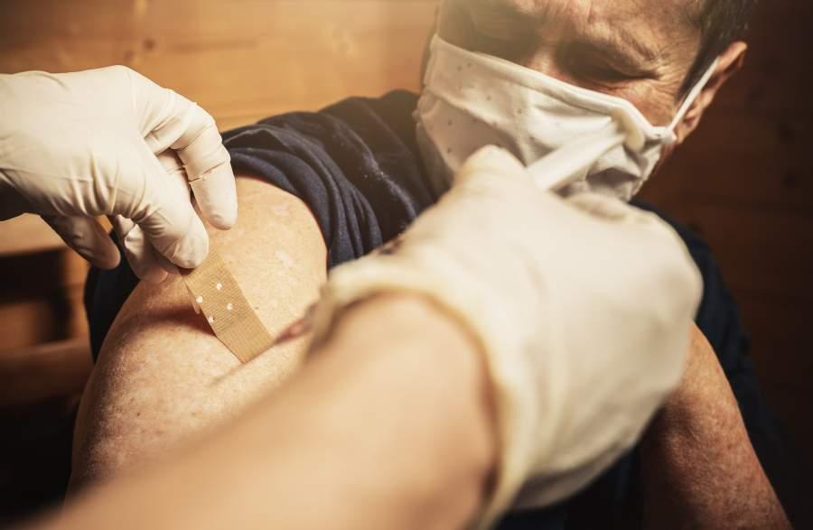 Person mit Mundnasenschutz bei einer Impfung zu Hause, jemand mit Gummihandschuhen klebt ein Pflaster auf den Arm