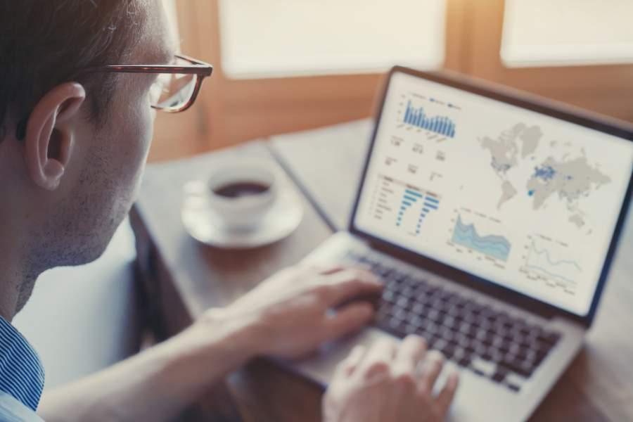 Blick über die Schulter eines Mannes, der an einem Tisch sitzt und am Laptop ein Dashboard mit einer Weltkarte mit farbig markierten Regionen betrachtet, daneben eine Kaffeetasse
