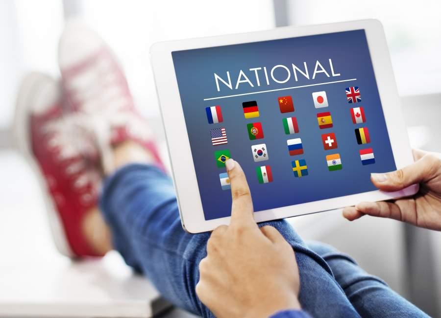 Person hält ein Tablet, auf dem zahlreiche Nationalflaggen zur Auswahl stehen, Schriftzug darüber: NATIONAL