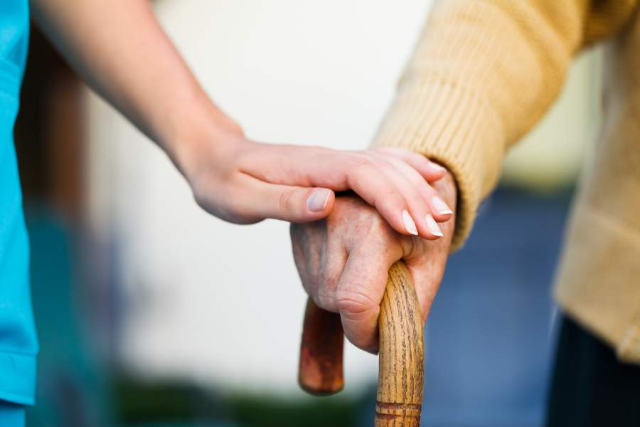 Altenpflegerin legt eine Hand auf die Hand einer alten Person, die eine Gehstock hält