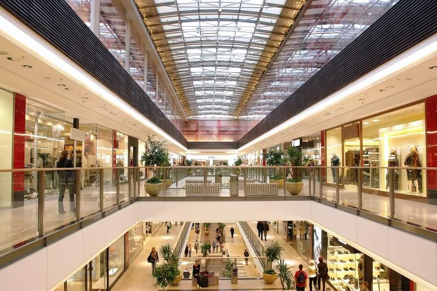 Mehrstöckiges Einkaufszentrum mit Galerien und Blick auf die unteren Etagen mit stationären Läden und Besucher:innen
