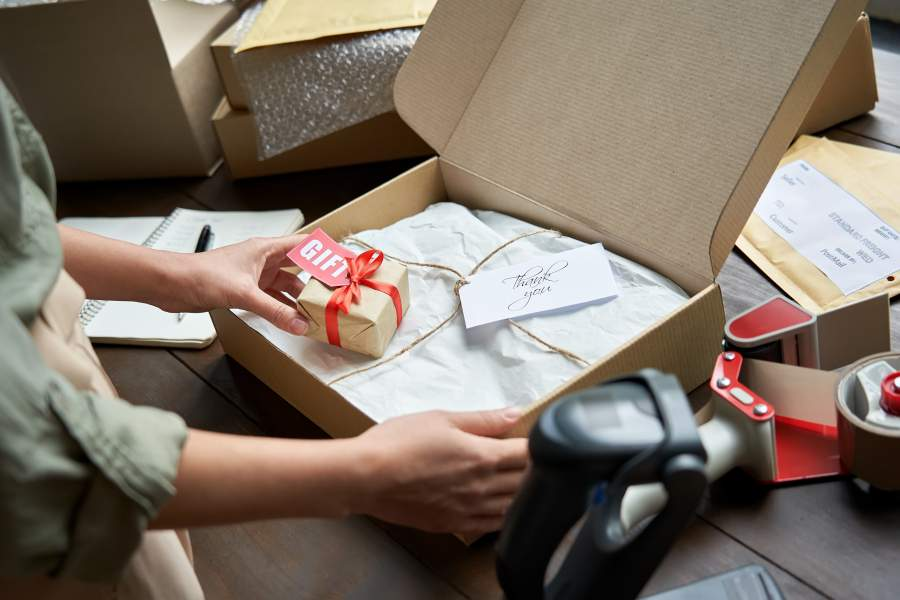Frau verpackt eine Online-Bestellung liebevoll in einem Karton und legt einen kleinen Werbeartikel als Geschenk bei