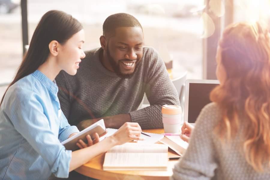 Internationale Studierende in einem fröhlichen Gespräch, auf dem Tisch sind Lernunterlagen und ein Kaffeebecher