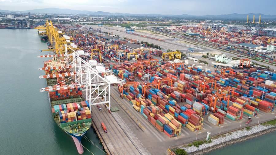 Vogelperspektive auf einen Container-Hafen mit zahlreichen Containern und beladenem Frachtschiff