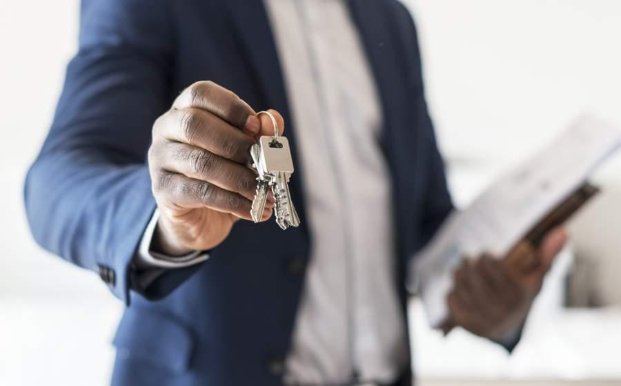 Person of Color in Business-Anzug mit Unterlagen hält einen Schlüsselbund für eine Immobilie in den Bildmittelpunkt