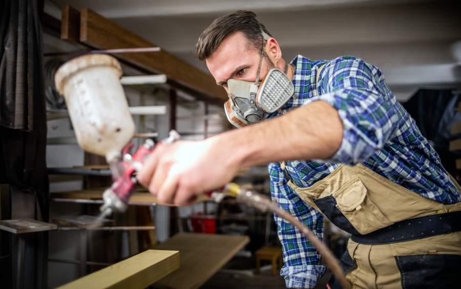 Handwerker bearbeitet Holz mit Sprühfarbe und trägt eine Atemschutzmaske zum Schutz vor Gesundheitsrisiken für die Atemwege