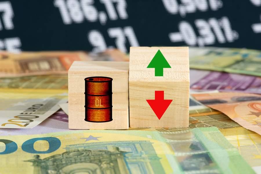 Zwei Würfel auf Geldscheinen, die sichtbaren Würfelflächen zeigen ein Ölfass sowie einen grünen Pfeil nach oben und einen roten Pfeil nach unten, im Hintergrund Börsenwerte